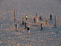 Elderly playing volleyball on isolated beach. Elderly people playing volleyball on isolated beach at sunset. Long shadows royalty free stock photos