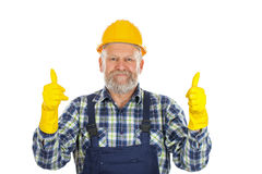 Elderly plumber showing thumbs up. Picture of an elderly plumber wearing yellow helmet and gloves, showing thumbs up Stock Photos