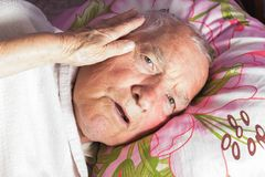 Elderly 80 plus year old man in a home bed. Illness, aging, unhealthy concepts Stock Photos