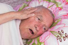 Elderly 80 plus year old man in a home bed. Illness, aging, unhealthy concepts Stock Photography