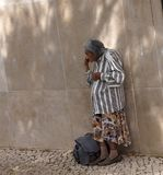 Elderly Portuguese Woman In Shade Of Building. Elderly Portuguese woman standing by building wall in the shade in Loule Portugal Royalty Free Stock Image