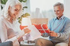 Elderly positive couple their opening gifts stock images