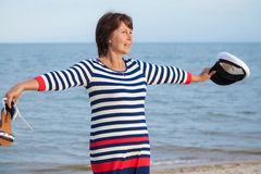 Elderly pretty woman enjoys relaxing by the sea Royalty Free Stock Photography