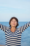 Elderly pretty woman enjoys relaxing by the sea Stock Photo