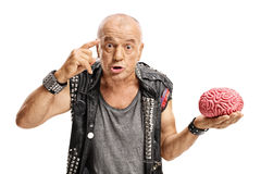 Elderly punker with brain model holding finger on his temple. Elderly punker with a brain model holding a finger on his temple asking do you have a brain royalty free stock photos