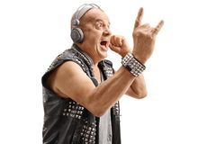 Elderly punker listening to music and making rock hand gesture. Elderly punker listening to music on headphones and making a rock hand gesture isolated on white royalty free stock image