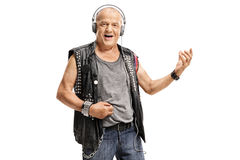 Elderly punker wearing headphones and playing air guitar. Isolated on white background stock photo