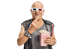 Elderly punker wearing a pair of 3D glasses and having popcorn. Isolated on white background royalty free stock images