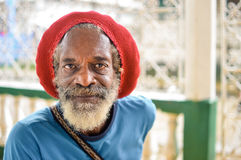 Elderly rasta man wears a red rasta hat which hides his long gre Royalty Free Stock Photos
