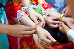 Elderly relatives presenting the golden bracelet as a blessing i Stock Image