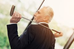 An elderly respectable man posing in his office with a golf club. He sits on the desktop behind the laptop Stock Photo