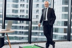 An elderly respectable man in a strict business suit posing in the office playing a mini golf game. He stands in the background of the window and holds a golf Stock Image