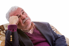 Elderly retired man relaxing in a chair. Elderly retired man relaxing in a comfortable armchair staring thoughtfully up into the air with an intent expression Stock Images
