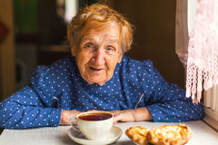 An elderly russian woman drinking tea at kitchen Stock Photography