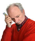 Elderly sad man with dollar bills Royalty Free Stock Images