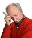 Elderly sad man with dollar bills Royalty Free Stock Images