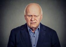 Elderly sad skeptical man looking down stock image