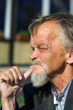 Elderly sad tramp. Stock Photos