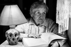 Elderly sad woman with a book. Black and white photo. Elderly woman with a book. Black and white photo Royalty Free Stock Photography