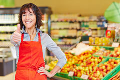 Elderly saleswoman holding thumbs up in supermarket Royalty Free Stock Photos