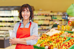 Elderly saleswoman in supermarket. Elderly smiling saleswoman standing with her arms crossed in a supermarket stock image