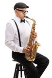 Elderly saxophonist sitting on a chair and playing Stock Image