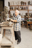 Elderly sculptor creates head Royalty Free Stock Photography
