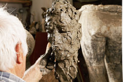 Elderly sculptor modelling sculpture Royalty Free Stock Image