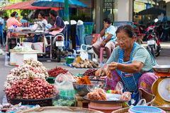 Elderly sell chili. PHICHIT THAILAND-JUNE 19: Elderly woman of Thailand is still trading onion, garlic and chilli in a bazaar on the road happily.On June 19 stock photo