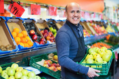 Elderly  seller offering seasonal ripe fruits in local grocery Stock Images