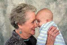 Elderly Senior and Baby. An elderly woman hold her great-grandson close to her face in a portrait Royalty Free Stock Images