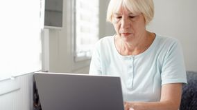 Elderly senior blond woman working on laptop computer at home. Remote freelance work on retirement. Elderly senior blond woman working on laptop computer at home stock footage