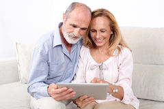 Elderly senior couple. Looking together at devise Stock Photography
