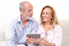 Elderly senior couple. Looking together at devise Royalty Free Stock Image