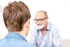 Elderly senior man listening and smiling Royalty Free Stock Photo