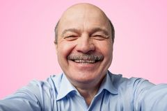 Elderly senior man with a mustache holding a smartphone and makes selfie. Smiling broadly on pink background royalty free stock photo