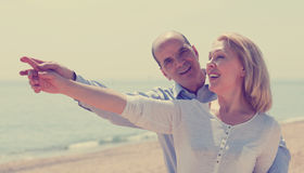 Elderly senior with mature woman at seashore vacation. Elderly senior with mature women at seashore vacation pointing fingers Royalty Free Stock Photos