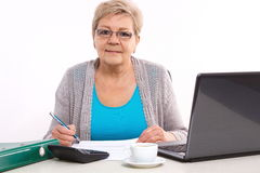 Elderly senior woman counting utility bills at her home, financial security in old age stock photo