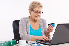 Elderly senior woman with credit card and laptop paying over internet for utility bills or online shopping Stock Photos