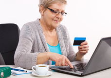 Elderly senior woman with credit card and laptop paying over internet for utility bills or online shopping Stock Image