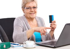 Elderly senior woman holding credit card and showing laptop screen, paying over internet for utility bills or shopping Stock Photo