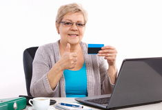 Elderly senior woman holding credit card and showing thumbs up, paying over internet for utility bills or shopping. Senior woman, an elderly pensioner holding Royalty Free Stock Photos