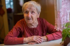 Elderly woman sitting at the table in home. Royalty Free Stock Images