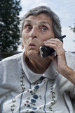 Elderly Senior Woman Talking on Phone. An elderly woman, with a look of surprise on her face, talks on a cordless phone stock image