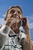 Elderly Senior Woman Using Cordless Phone. An elderly, female senior citizen chats on a modern, cordless telephone on a sunny day stock image