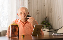 Elderly Shaving his Beard with Oil and Mirror Royalty Free Stock Images