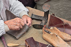 Elderly shoemaker makes artisan shoes royalty free stock photos