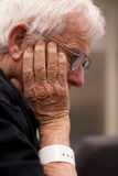 Elderly sick hospital patient wearing wristband. Profile portrait of a senior citizen (male) sits with his hand holding his head.  He wears a hospital ID Royalty Free Stock Images