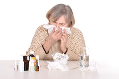 Elderly sick woman blow ones nose Royalty Free Stock Images