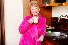 Elderly smile woman drinking coffee or tea in her kitchen Royalty Free Stock Photography